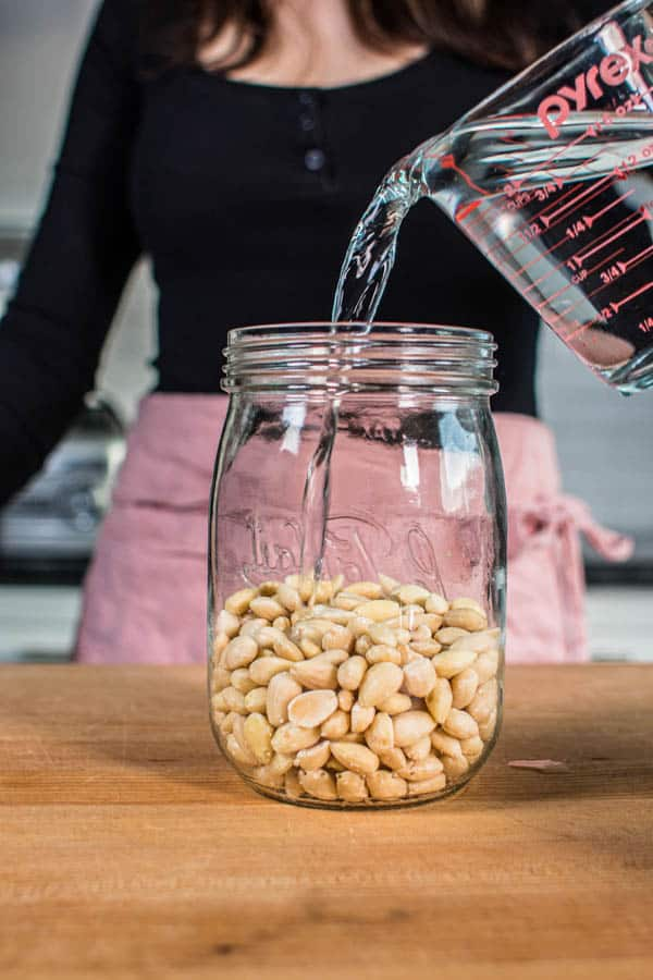 Pouring filtered water over blanche almonds to soak for almond milk.