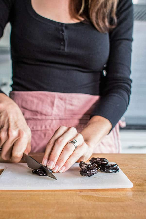 A woman chopping prunes to sweeten almond milk. This is how to make almond milk at home.