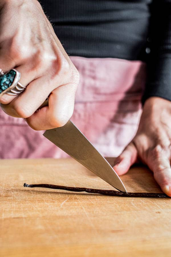 A vanilla bean pod being sliced open with a pairing knife to harvest the vanilla beans. This is how to make almond milk at home!