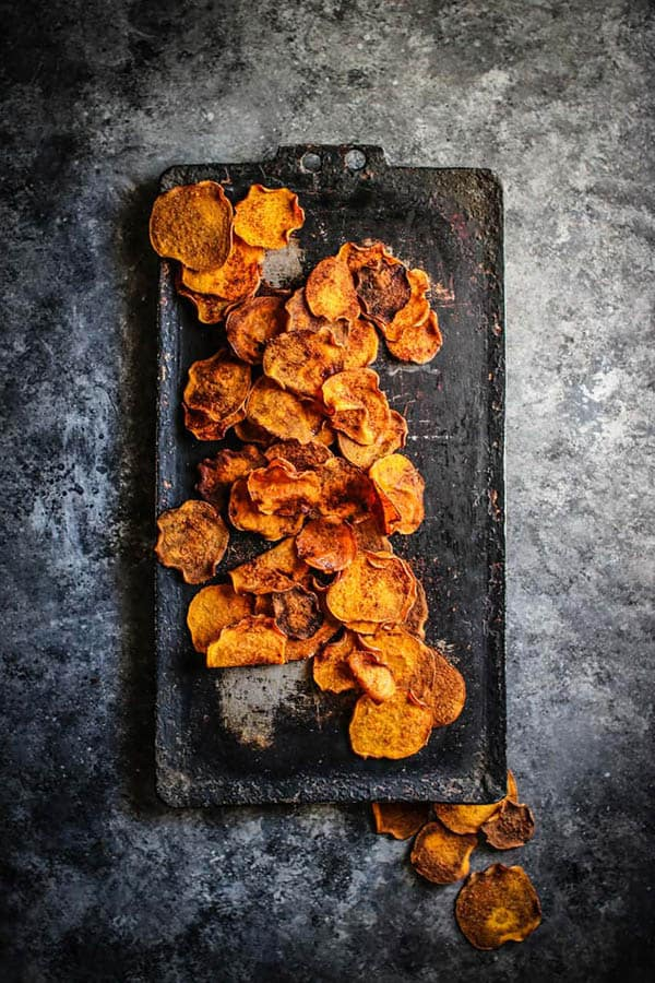 A scattering of golden, Honey BBQ Sweetpotato Chips on a black serving tray .