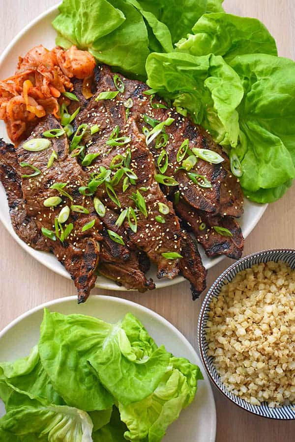 A close up of a platter of Kalbi recipe served with lettuce cups, cauliflower rice and kimchi.