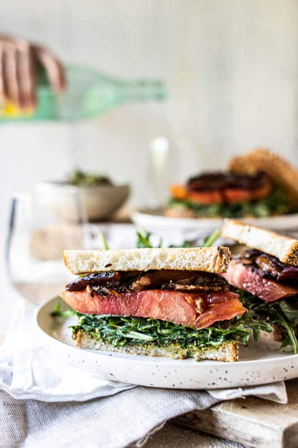 A halved Ultimate California Grown BLT sandwich on a plate with an arugula salad. A woman is pouring a glass of sparkling water in the background.