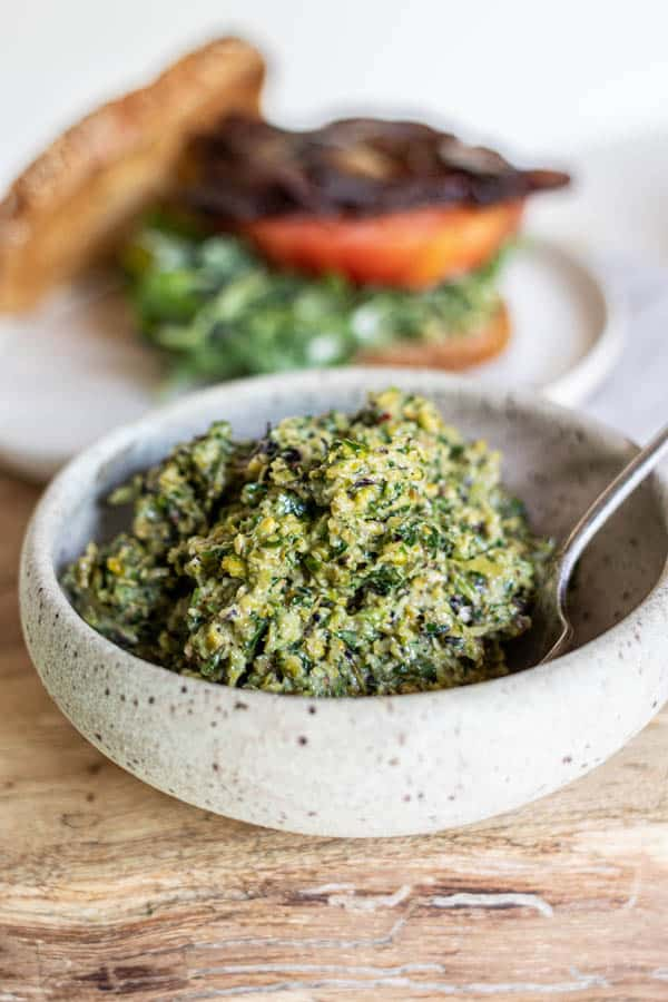 A bowl of grilled asparagus pistachio pesto for a BLT sandwich.