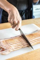 Bacon for a BLT sandwich being sliced in half to create eggplant bacon weaves.
