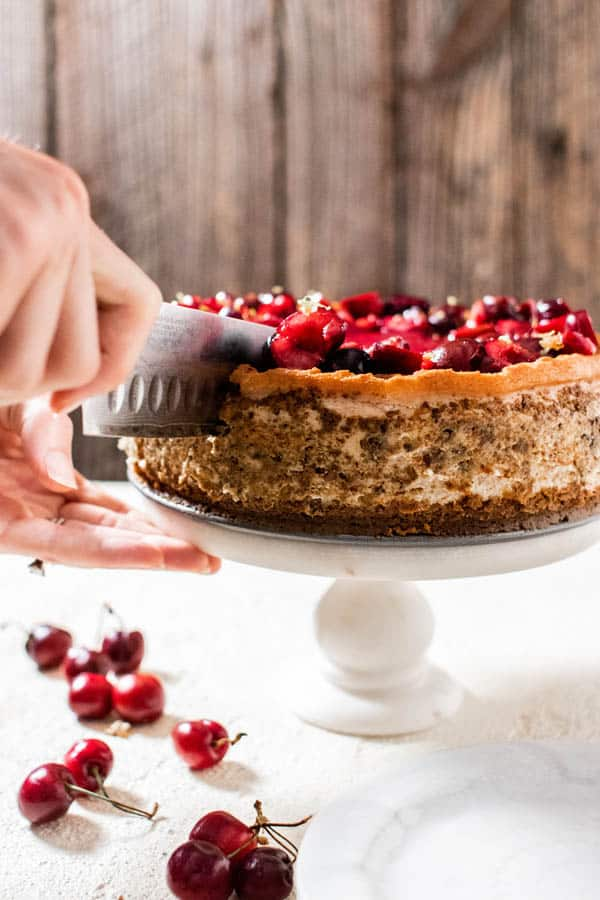 A sideview of Fresh Cherry Cheesecake. The outside walls of the cheesecake have a pistachio crumble adhered to them. A knife is slicing into the cheesecake to cut a slice.