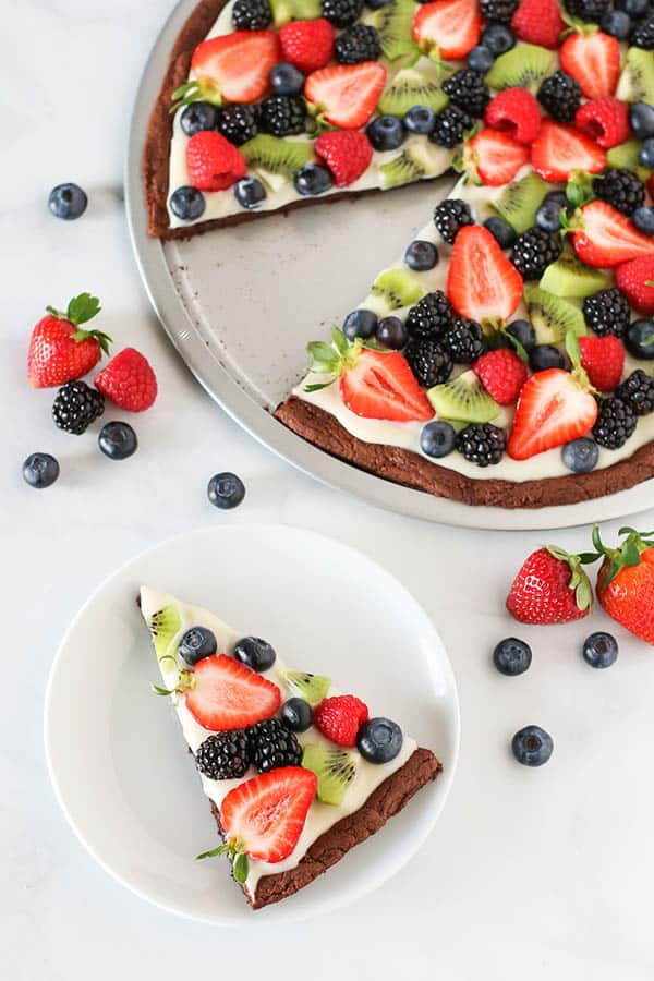 A round Brownie Fruit Pizza  topped with a vegan whipped topping