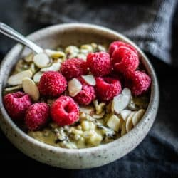 A bowl of Pistachio Wild Rice Pudding topped with raspberries and almonds. this easy recipe for rice pudding is worth the effort.