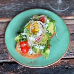 finished avocado toast with fried egg, arugula, tomatoes, olive oil