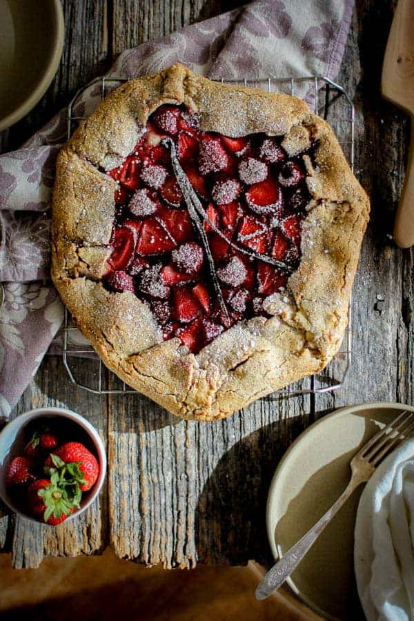 A rustic strawberry galette topped with confectioners sugar.