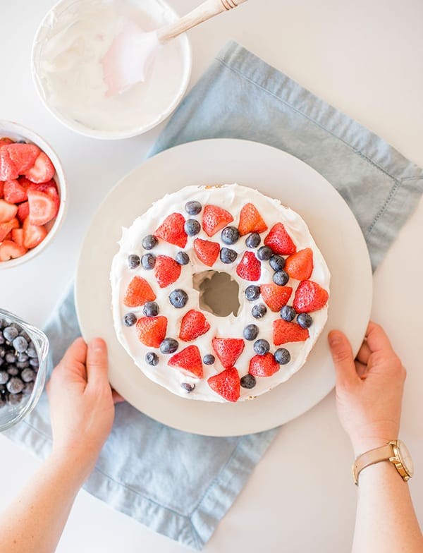 A store bought angel food cake iced with whipped cream and topped with fresh berries for a  simplered, white and blue dessert cake.
