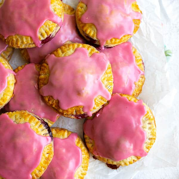A pile of round cherry hand pies topped with pink cherry frosting.