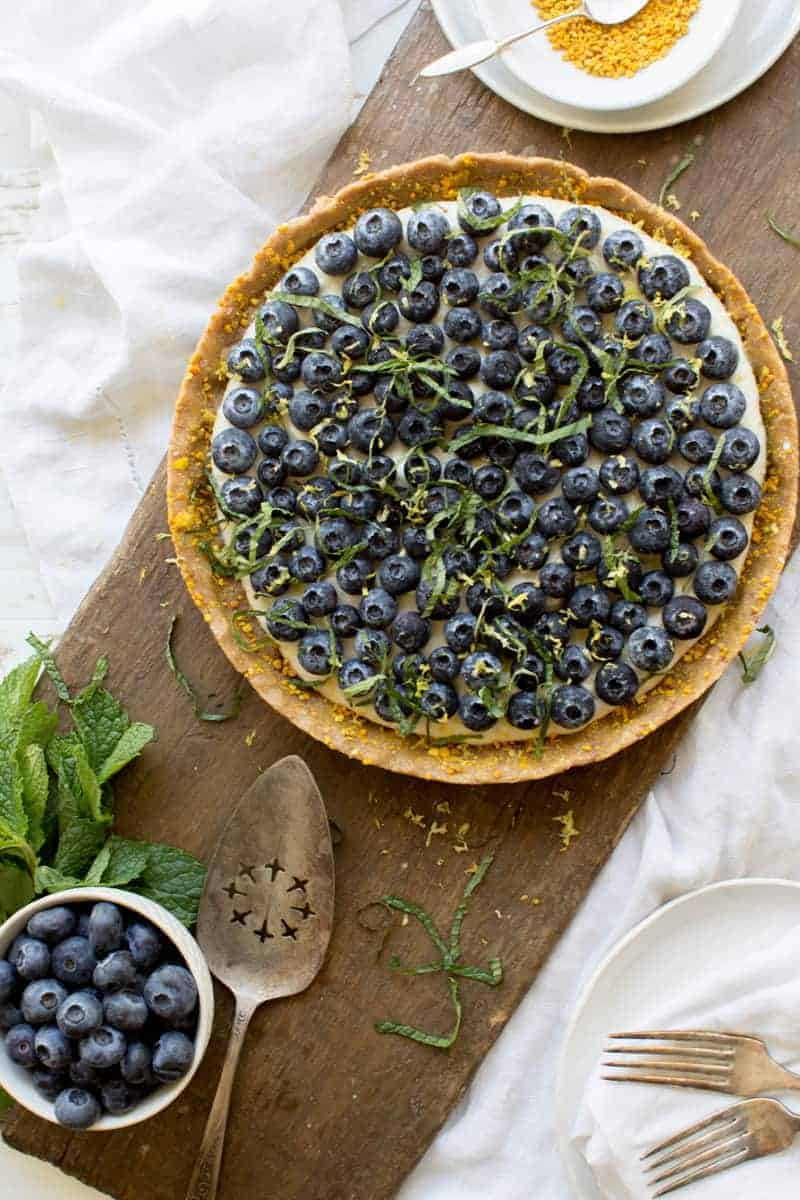 A raw dessert pizza with fresh blueberries, lemon zest, and mint.