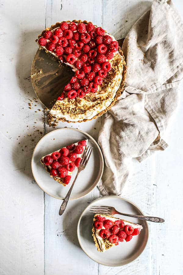 A Mascarpone tart topped with fresh raspberries and pistachio crumble.