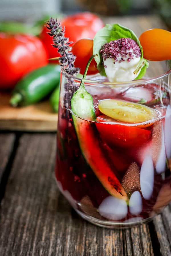 A wine cocktail with halved peppers, cherry tomatoes and basil sprig garnishes