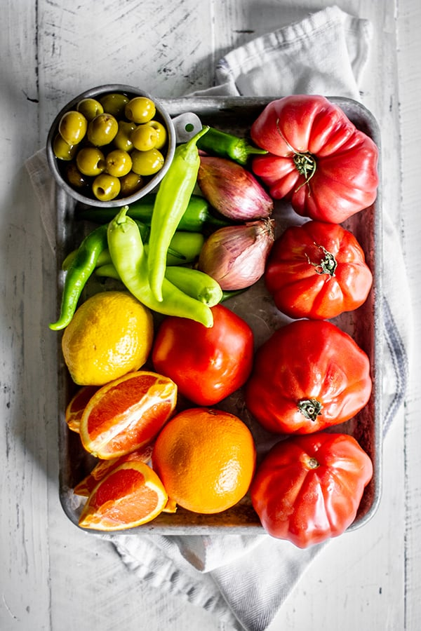 All of the fresh ingredients needed to make our homemade Bloody Mary mix recipe. Tomatoes, peppers, oranges, olives, lemons and shallots.