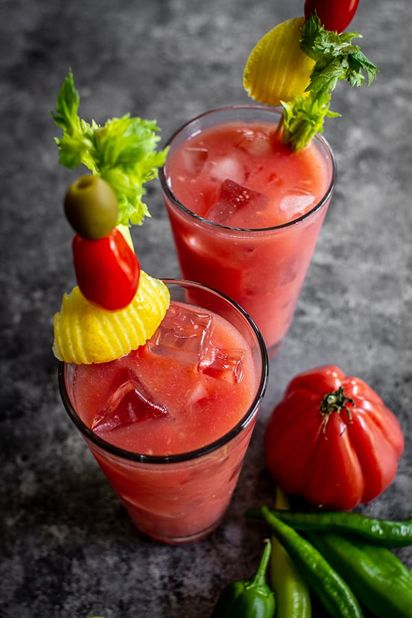 2 Bloody Mary's styled with skewers made with green olives, cherry tomatoes and lemon wheels.