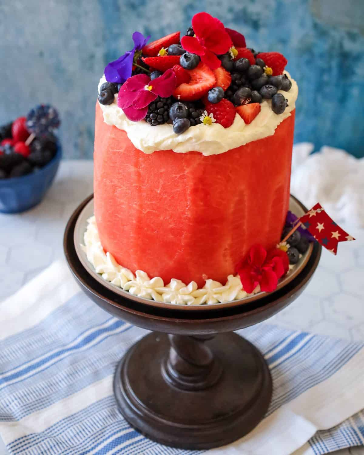 A peeled watermelon arranged o a cake platter and carved to look like a cake. the cake is iced with fresh whipped cream, strawberries, blueberries and blackberries for a fresh spin on a red, white and blue dessert cake!