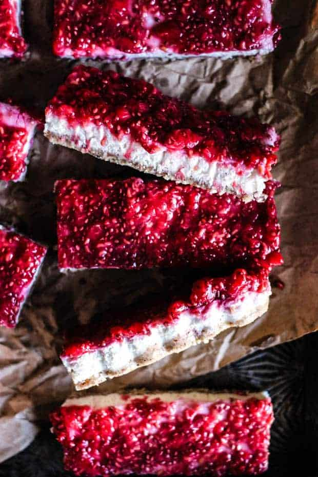 Five Paloe raspberry bars sliced on a piece of parchment paper. The bars have a light colored crust, a white filling and a bright red fresh raspberry chia jam topping.