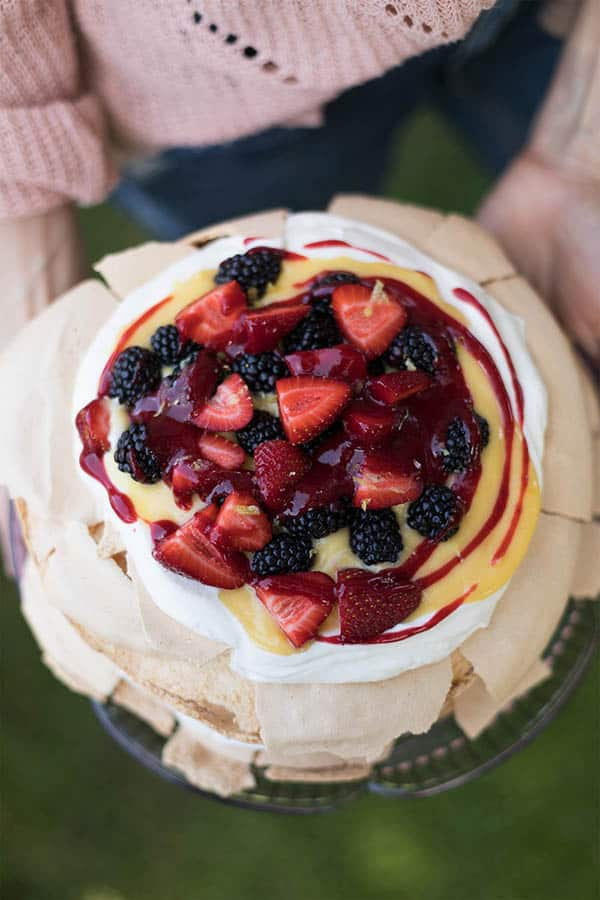 A layered pavlova topped with whipped mascarpone cream, lemon curd, a red berry sauce, and fresh strawberries and blackberries.