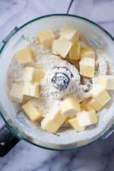 Chunks of butter in a food processor to make a walnut tart recipe.