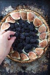 Figs and blackberries arranged on tart.