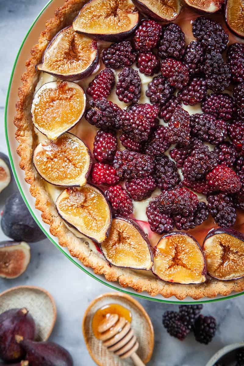 A close of our berry fig tart recipe. It is a walnut crust with a creamy filling that is topped with blackberries and figs.