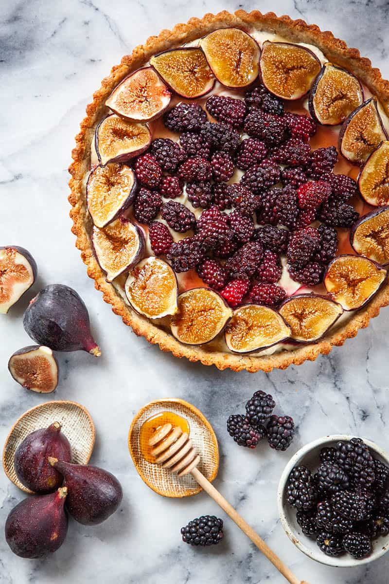 Berry Fig Tart recipe ready to serve with honey for drizzling.