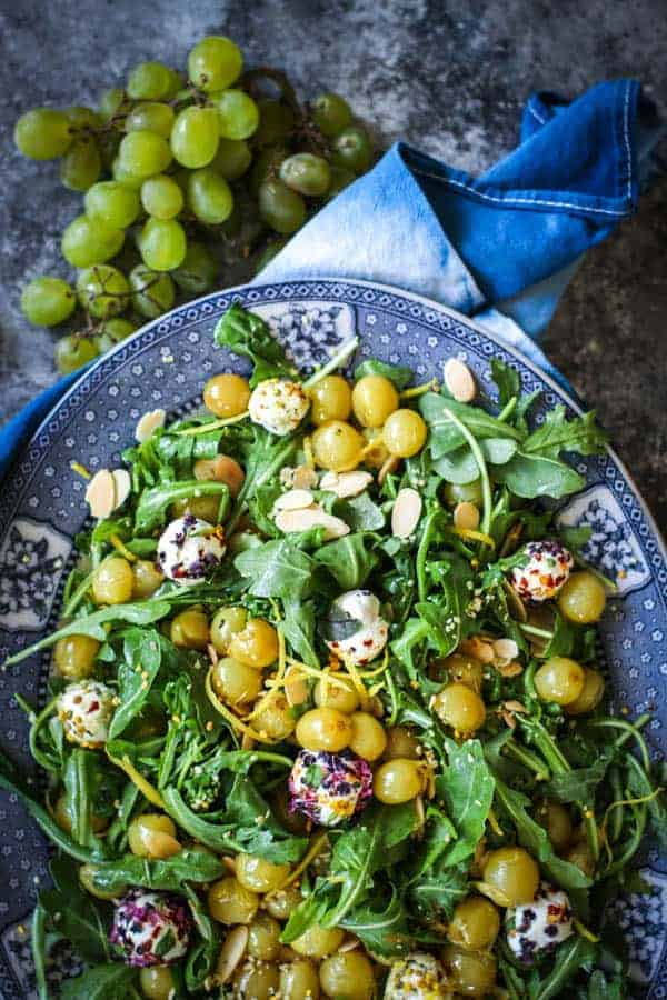 A platter of arugula, goat cheese and roasted grape salad.