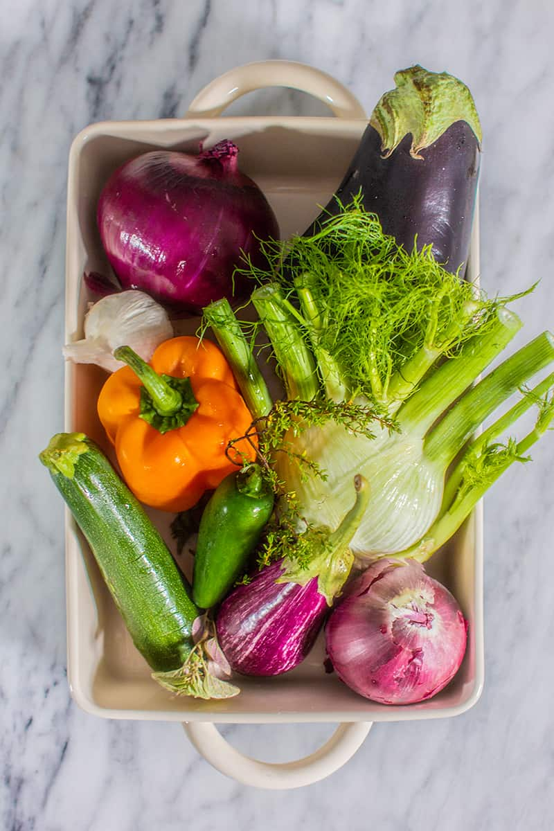 A variety of fresh vegetables to make caponata of eggplant in a roasting dish. There is fennel, eggplant, peppers, zucchini, onions and garlic.