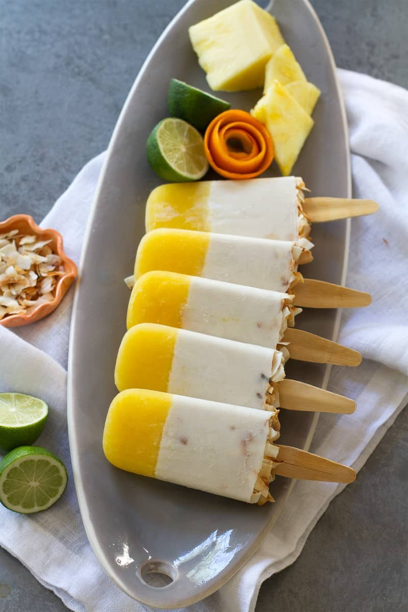 A layered homemade popsicle recipe with a white lower level and a yellow upper level.