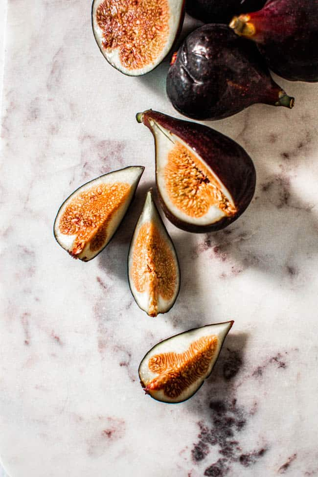 Fresh purple figs that have had quarters cut out of them revealing the pink flesh inside.