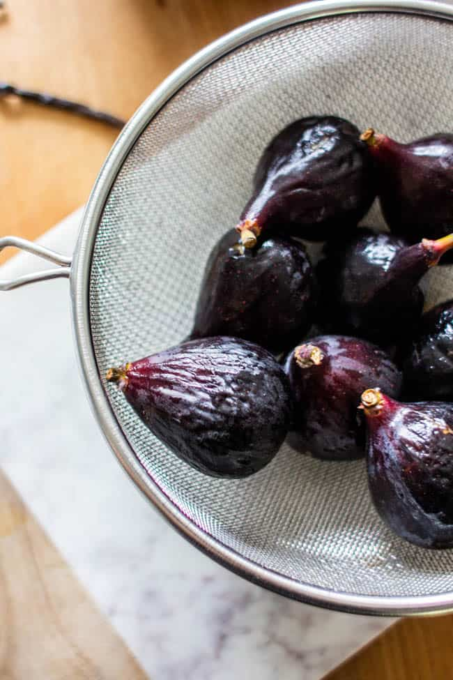 Fresh figs in a strainer after being washed.
