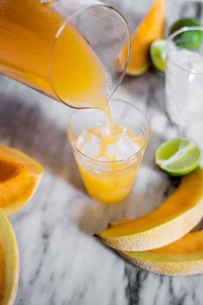 Pouring a glass of cantaloupe agua fresca.