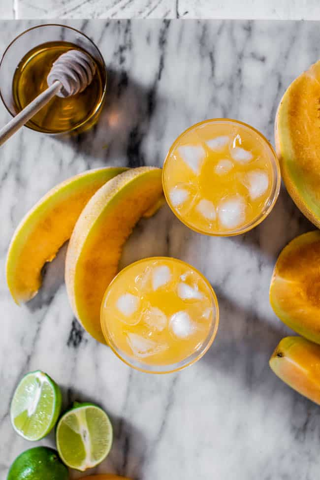 Two glasses of Cantaloupe Agua Fresca with ice on a marble board with lime halves and cantaloupe wedges.