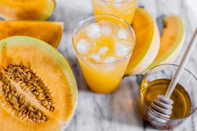 A glass of our Cantaloupe Agua Fresca recipe next to half a cantaloupe and a jar of honey.