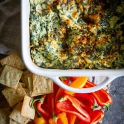A baking pan fresh out of the oven filled with A Classic Artichoke and Spinach Dip Recipe. There are crackers and mini bell peppers for dipping.