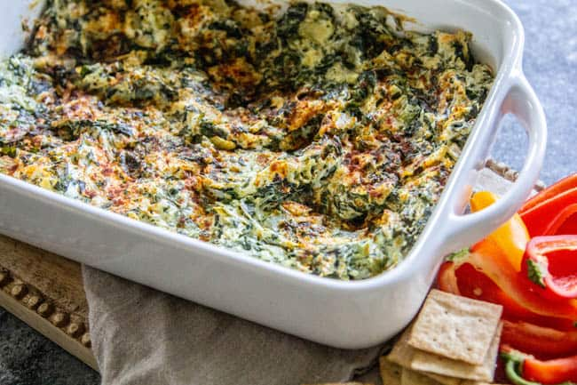 A Classic Artichoke and Spinach Dip Recipe served with crackers and halved bell peppers.