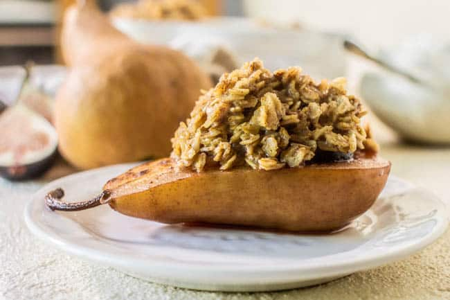 A roasted pear half on a serving  plate piled high with oatmeal. This Recipe for Baked Oatmeal Fig Stuffed Pears has a fig nestled inside the pear.