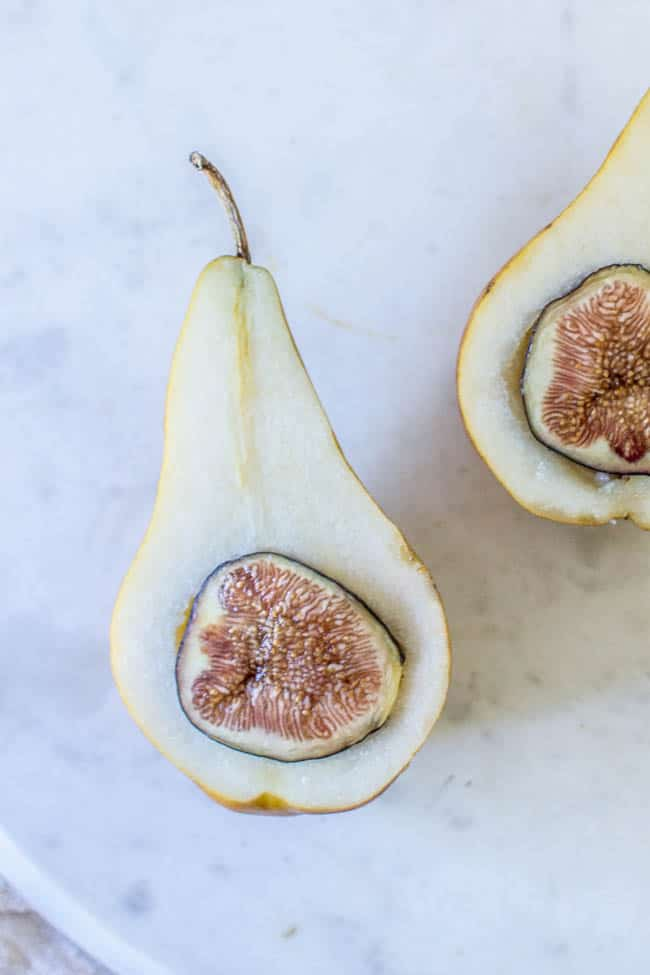 A pear that has been sliced in half and had the seeds and core removed. Half of a fresh fig is nestled inside each pear half. This is the first step in thsi recipe for baked oatmeal and fig stuffed pears..