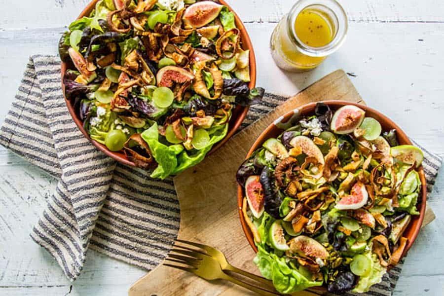 Two bowls of Fresh Fig & Grape Salad with Crispy Shallots and a jar of honey mustard vinaigrette on a table ready to serve.
